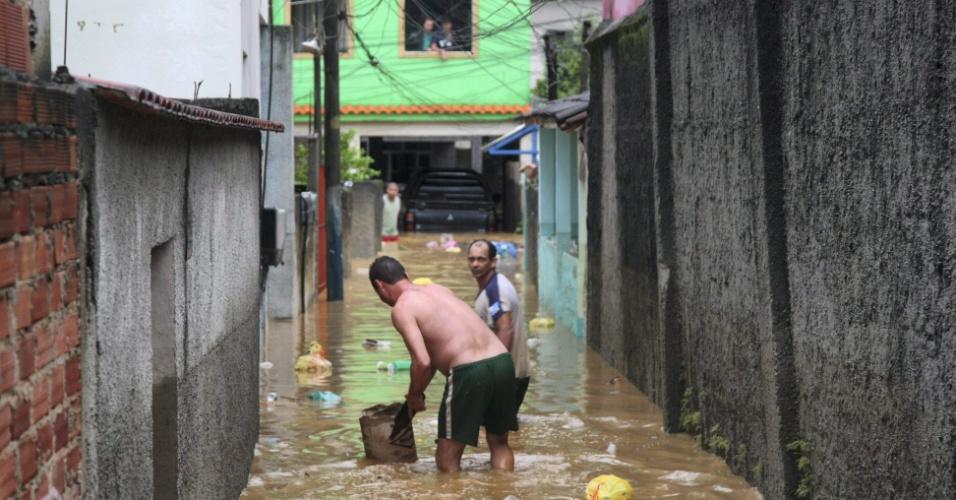 3.jan.2013 - Moradores passam por viela alagada, no bairro de Xerém, em Duque de Caxias (RJ). Um homem morreu, após o desabamento de uma casa. Cerca de cem pessoas foram desalojadas, segundo a Defesa Civil