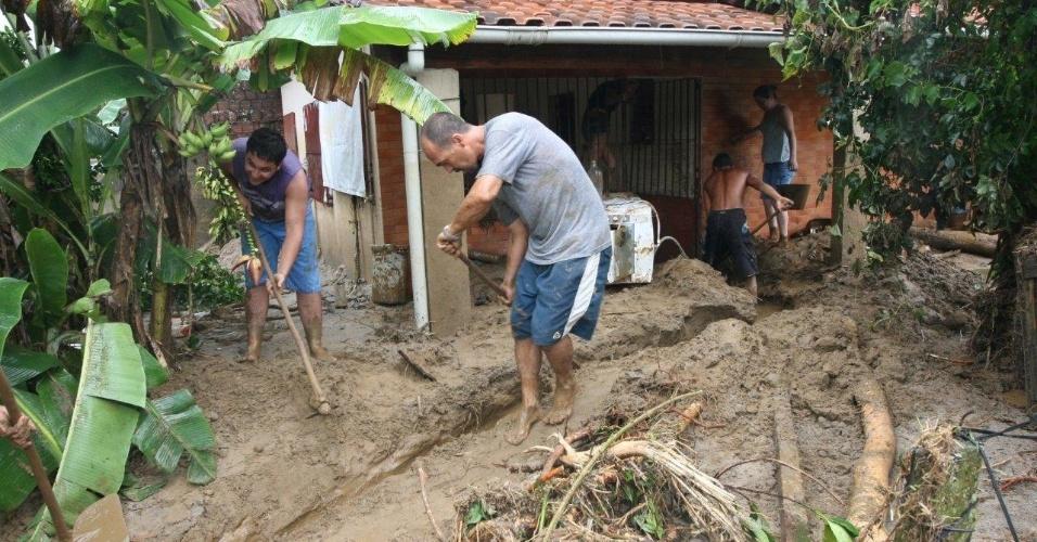 3.jan.2013 - Moradores cavam caminho para escoamento de água, em meio ao barro deixado pela enchente após temporal que caiu durante a madrugada no bairro de Xerém, em Duque de Caxias (RJ)