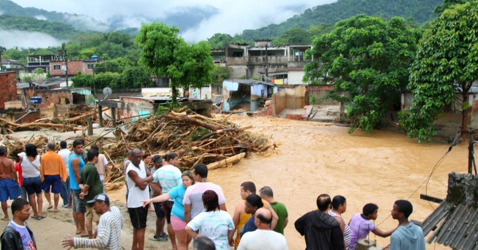 3.jan.2013 - Moradores do bairro Café Torrado, no distrito de Xerém, em Duque de Caxias (RJ), observam enchente após forte chuva que ocorreu durante a madrugada. Um homem morreu, após o desabamento de uma casa e cerca de cem pessoas foram desalojadas, segundo a Defesa Civil