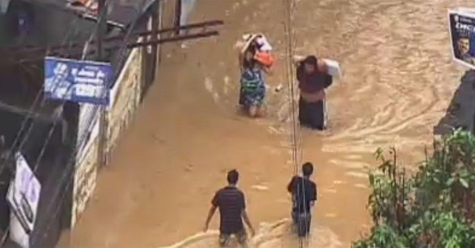 3.jan.2013 - Moradores tentam atravessar rua alagada, no bairro de Xerém, em Duque de Caxias