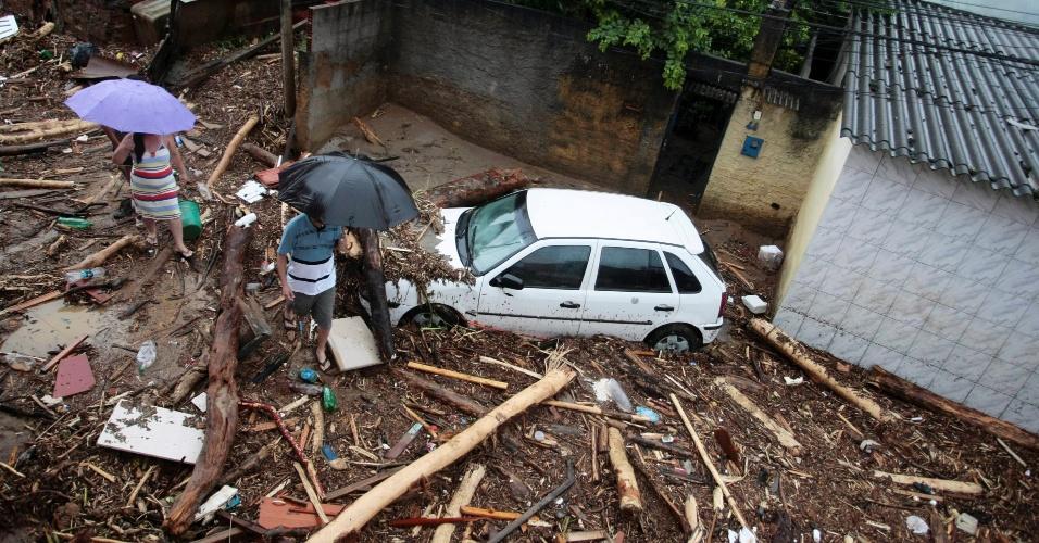 3.jan.2013 - Moradores caminham sobre escombros deixados por enchente no bairro de Xerém, em Duque de Caxias (RJ). Um temporal que caiu durante a madrugada alagou ruas e destruiu casas