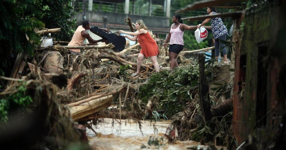 3.jan.2013 - Moradores tentam salvar pertences no bairro de Xerém, em Duque de Caxias (RJ). Um temporal que caiu durante a madrugada alagou ruas e destruiu casas