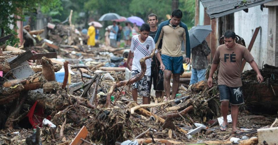 3.jan.2013 - Pessoas tentam passar por rua destruída após temporal que caiu durante a madrugada no bairro de Xerém, em Duque de Caxias (RJ)