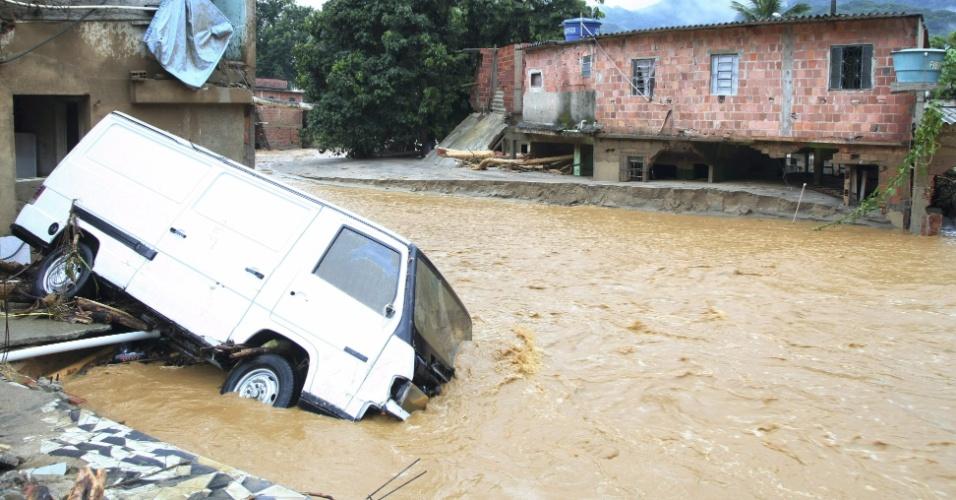 3.jan.2013 - Van cai em rua alagada do bairro de Xerém, em Duque de Caxias (RJ), após forte chuva que caiu durante a madrugada. Um homem morreu, após o desabamento de uma casa. Cerca de cem pessoas foram desalojadas, segundo a Defesa Civil