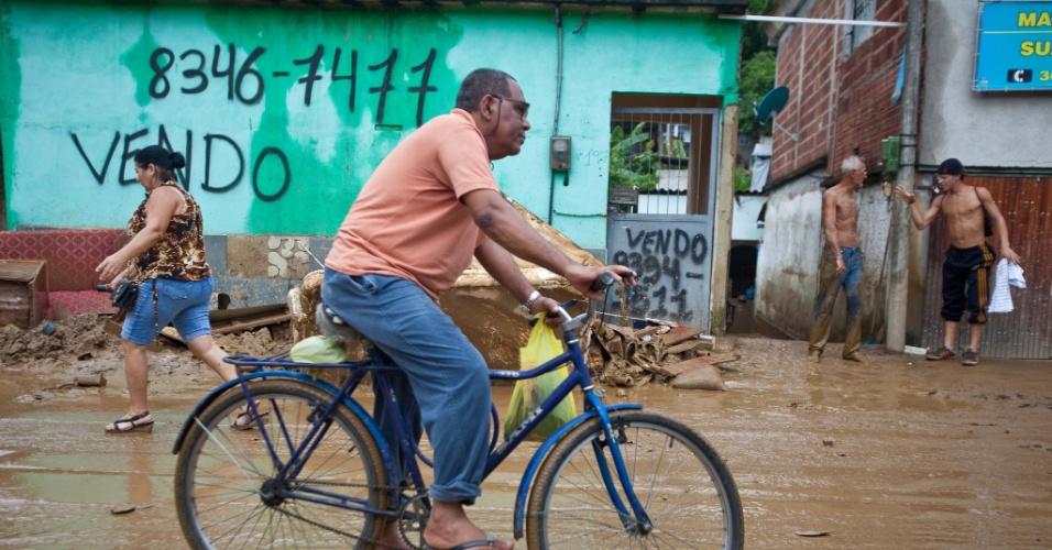 4.jan.2013 - Homem anda de bicicleta em rua tomada por lama, após a tragédia em Xerém, Duque de Caxias (RJ). Pelo menos 300 pessoas foram desalojadas e uma pessoa morreu durante as enchentes