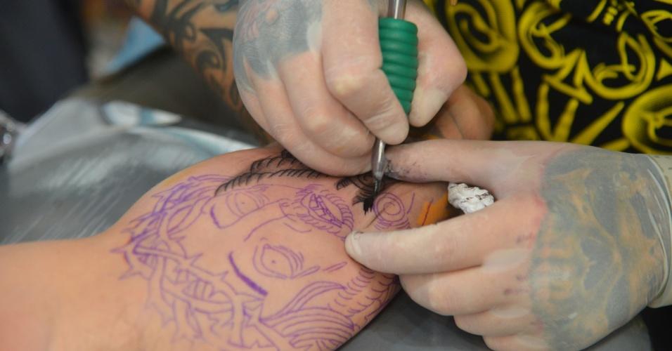 4.jan.2013 - Um tatuador trabalha durante feira internacional no Rio de Janeiro. O evento reúne cerca de mil tatuadores, artistas plásticos e body piercings, entre esta sexta-feira (4) e o domingo (6)