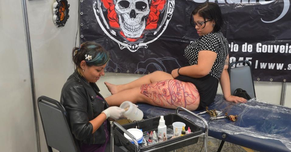4.jan.2013 - Uma tatuadora trabalha durante feira internacional no Rio de Janeiro. A Tattoo Week reúne cerca de mil tatuadores, artistas plásticos e body piercings, entre esta sexta-feira (4) e o domingo (6)