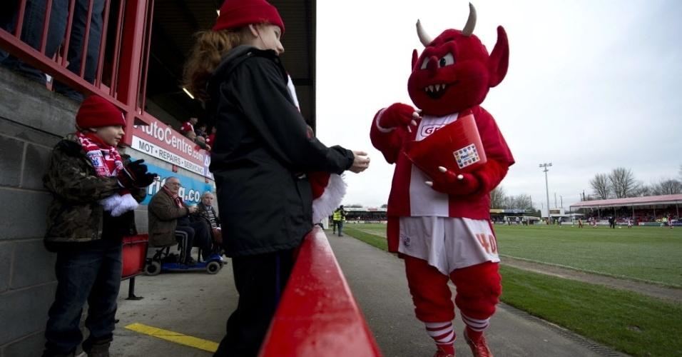05.jan.2013 - Reggie, o diabinho mascote do Crawley Town, distribui doces para crianças durante partida da equipe contra Reading, pela copa da Inglaterra