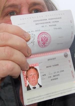 O francês Gerard Depardieu mostra seu novo passaporte com a nacionalidade russa no aeroporto de Mordóvia, a 640 km de Moscou