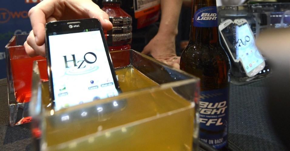 6.jan.2013 - Antes da abertura da feira, a empresa HzO Waterblock apresentou uma tecnologia que faz o smartphone resistir à água e também cerveja (na imagem, o aparelho é mergulhado em um recipiente de cerveja). A tecnologia chamada WaterBlock, explica a empresa, consiste em uma solução de vapor de elementos químicos que protegem o aparelho