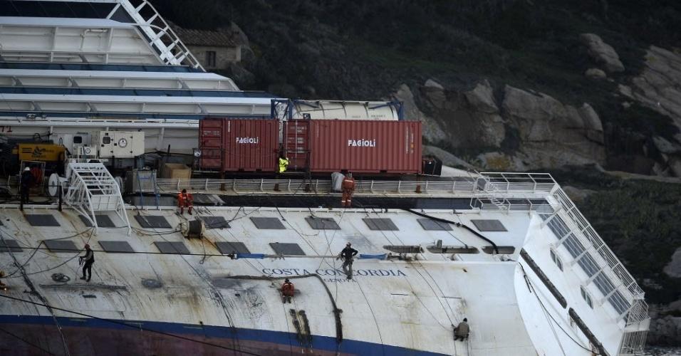 """7.jan.2013 -  Homens trabalham no navio Costa Concordia, que encalhou há um ano na ilha  Giglio, na Toscana (Itália).  O Costa Concordia transportava 4.229 pessoas, entre elas mais de 3.200 passageiros. Trinta e duas pessoas morreram no naufrágio e os corpos de duas vítimas nunca foram encontrados. Nesta segunda-feira (7), Francesco Schettino, o capitão do navio, queixou-se de ser """"retratado como alguém pior do que Bin Laden"""", em uma entrevista ao jornal """"La Stampa"""". Ele é é acusado pela justiça por naufrágio, homicídios por negligência e por abandonar o navio, tendo deixado o Costa Concordia antes da evacuação ser concluída"""