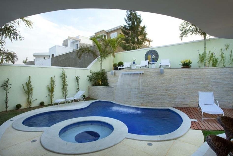 Nessa residência em Campinas (SP), a piscina de formas orgânicas recebeu cascata instalada no muro de arrimo, também aproveitado como solário. O projeto é do arquiteto Aquiles Kílaris