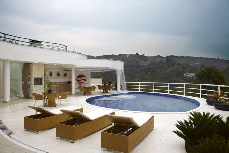 O projeto do arquiteto Aquiles Kílaris para essa residência buscou integrar a piscina com a exuberante natureza em redor. A cascata foi instalada na laje que cobre parte da área de lazer