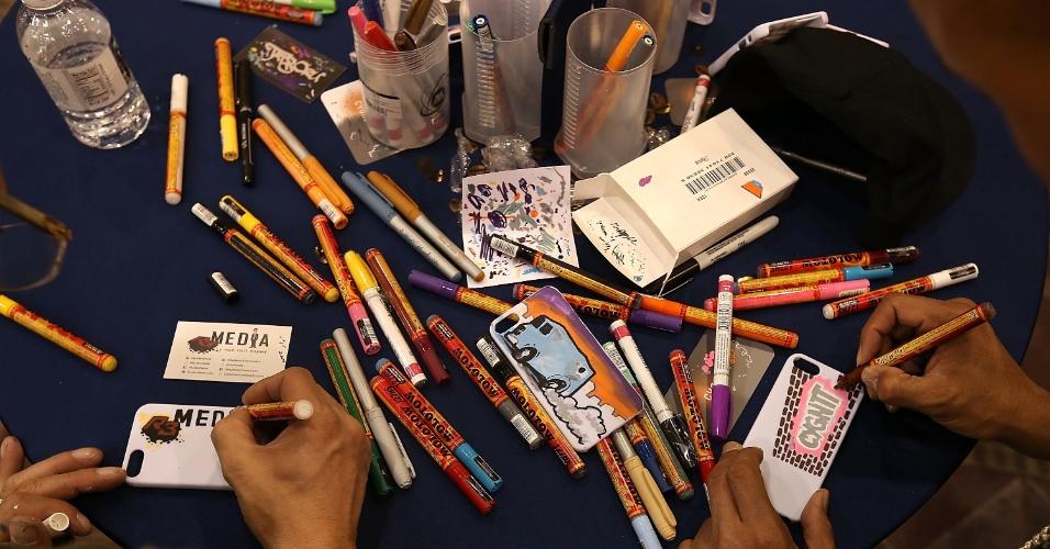 8.jan.2013 - Empresa Cygnett permite que visitantes customizem capinhas de celular com desenhos de artistas presentes no evento
