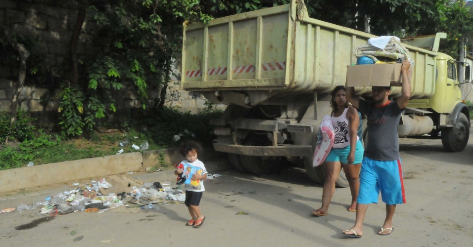 8.jan.2013 - Moradores de Xerém, em Duque de Caxias (RJ), carregam pertences enquanto caminham em meio à poeira e ao lixo resultantes das enchentes que castigaram a região. A prefeitura estima que serão necessários R$ 30 milhões para a reconstrução do distrito