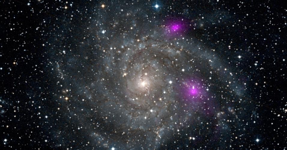 8.jan.2013 - O observatório espacial de raios X NuStar detectou dois buracos negros (pontos roxos) na galáxia espiral IC 342, que fica na constelação da Girafa (Camelopardalis), a 7 milhões de anos-luz de distância da Terra. Os dois aparecem muito mais brilhantes e claramente do que outros buracos negros de tamanhos semelhantes - provendo o primeiro dos muitos mistérios que a equipe do NuSTAR espera resolver