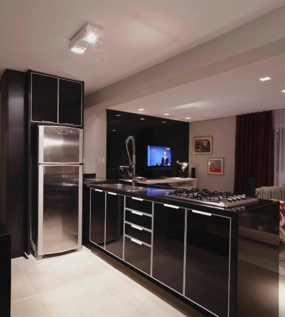 Os arquitetos Adine Woda e Artur Ferreira acoplaram o cooktop e a cuba à bancada, aproveitando o nicho para embutir os armários (Favo). Sobre a geladeira, mais um armário foi instalado e otimiza com eficiência o espaço disponível