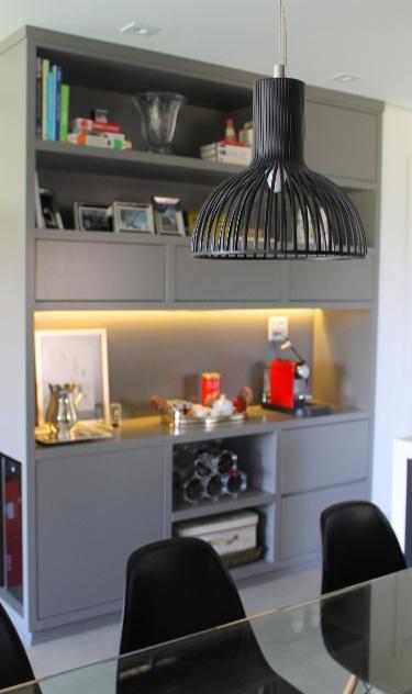 Complementando a área de refeições, idealizada pela arquiteta Camila Gazola, um armário em laca apoia a cafeteira, resguarda louças e objetos de cozinha e ainda serve de adega à sala integrada