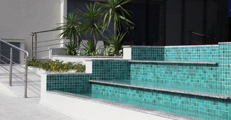 Com um espaço em desnível à disposição, o arquiteto Marcos Contrera criou um espelho d'água em forma de cascata, com degraus revestidos de pastilhas em tom de turquesa e soleiras de granito cinza