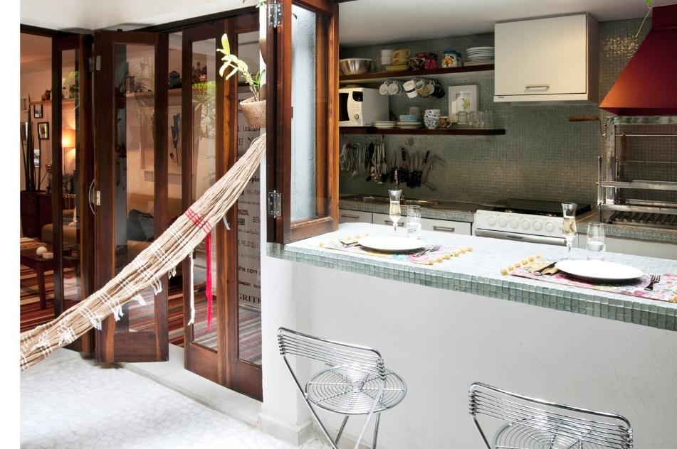 O canto para refeições que se divide entre a cozinha e a varanda foi criado pela arquiteta Crisa Santos com a abertura de uma janela do tipo camarão sobre o balcão revestido com as mesmas pastilhas (Vidrotil) adotadas na parede da cozinha. Para o conforto dos comensais a arquiteta optou pelas banquetas aramadas (Spicy)