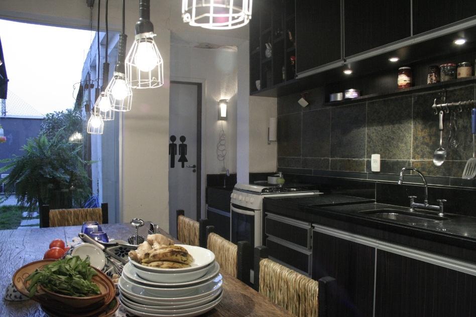 No projeto do arquiteto Nelson Wong, a área da cozinha (25 m²) integra-se à de convivência (40 m²) por meio da ampla mesa de jantar. Em estilo rústico, o ambiente tem piso de ardósia que sobe a parede protegendo a área da pia da umidade. Os armários em laminado e a bancada em granito preto acompanham a pintura do teto