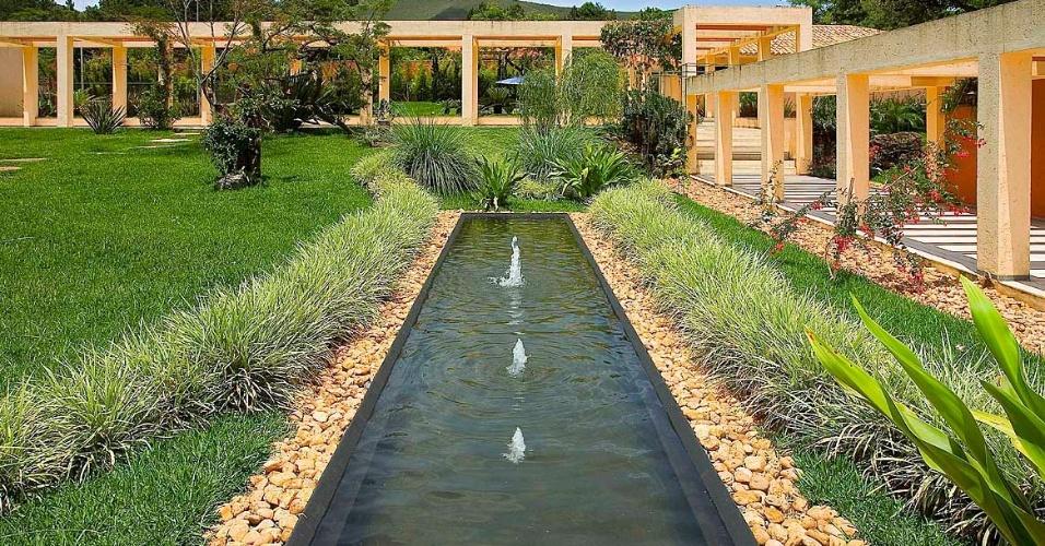 O espelho d'água suaviza a paisagem deste amplo jardim com gramado e caminho pergolado. Os jatos de água proporcionam movimento ao conjunto criado pelo paisagista Erly Hooper