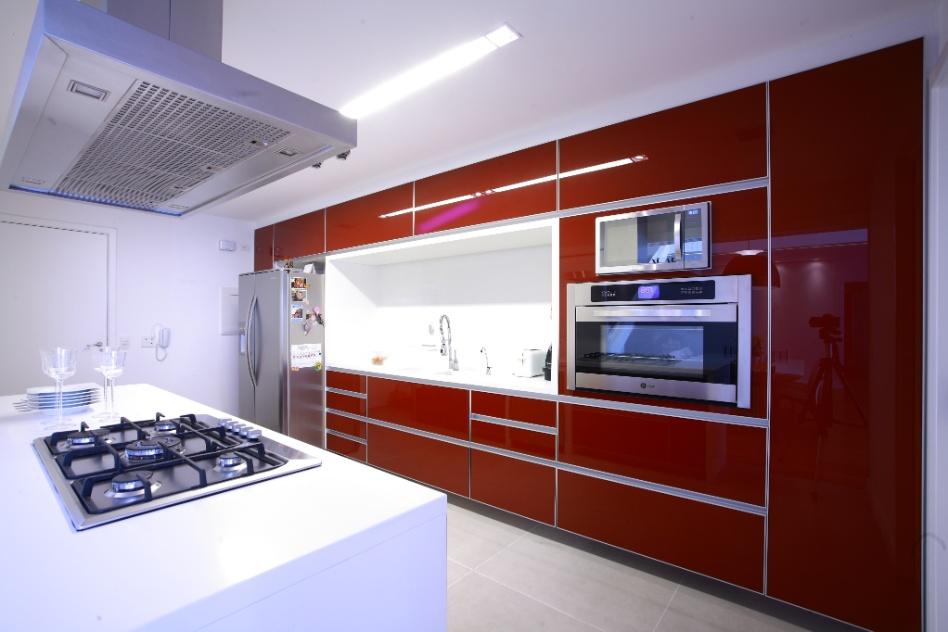 Note que os armários vermelhos da cozinha americana idealizada pela arquiteta Paula Andrade destacam-se na ambientação que majora os tons claros