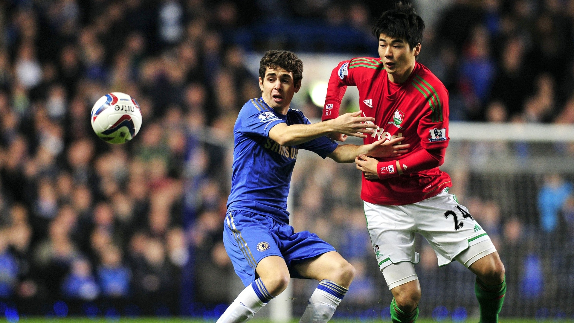 09.jan.2013 - Meia brasileiro Oscar, do Chelsea, disputa a posse da bola com Ki Sung-Yueng, do Swansea