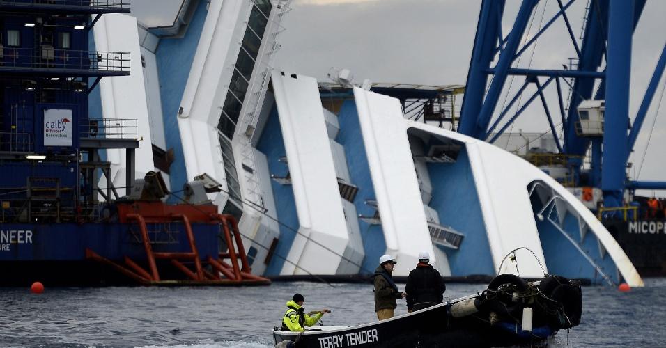 10.jan.2013 - Trabalhadores em um barco passam perto do navio Costa Concordia, encalhado perto do porto da ilha italiana de Giglio. Um ano depois do naufrágio que matou 32 pessoas, a embarcação continua atracada na ilha