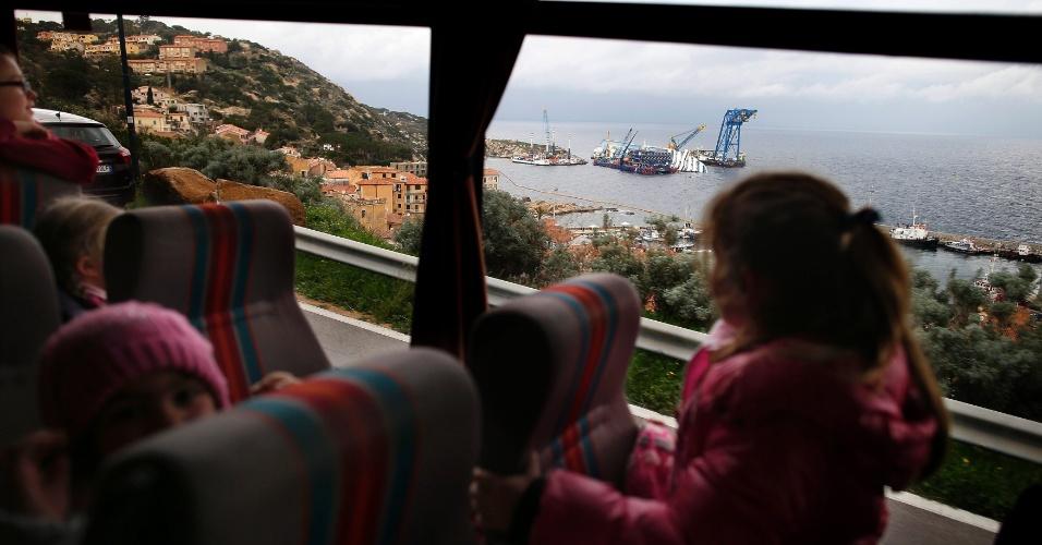 11.jan.2013 - De dentro de ônibus criança observa o navio Costa Concordia, que segue encalhado perto do porto da ilha italiana de Giglio quase um ano depois do naufrágio que matou 32 pessoas. Equipes de resgate trabalham na remoção da embarcação, que deve ser retirada do local no final do ano