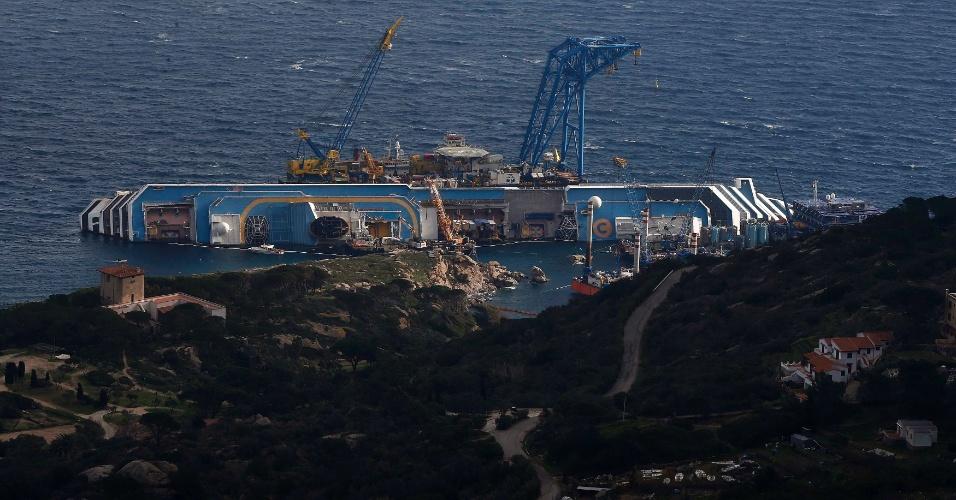 11.jan.2013 - O navio Costa Concordia, encalhado perto do porto da ilha italiana de Giglio, é cercado por guindastes e equipamentos de resgate. Quase um ano depois do naufrágio que matou 32 pessoas a embarcação continua no local. A expectativa é que ele seja removido até o final do ano