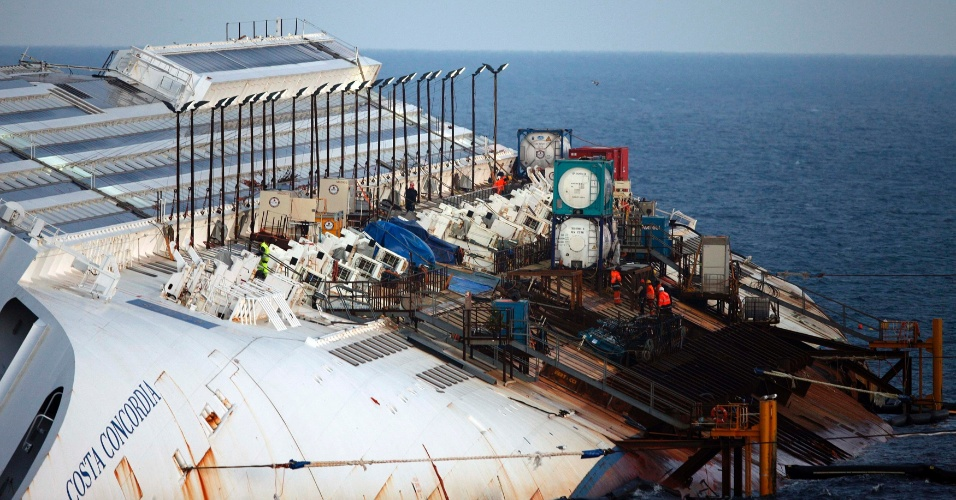 11.jan.2013 - Trabalhadores caminham sobre o casco do navio Costa Concordia, encalhado perto do porto da ilha italiana de Giglio. Quase um ano depois do naufrágio que matou 32 pessoas, a embarcação continua atracada no local