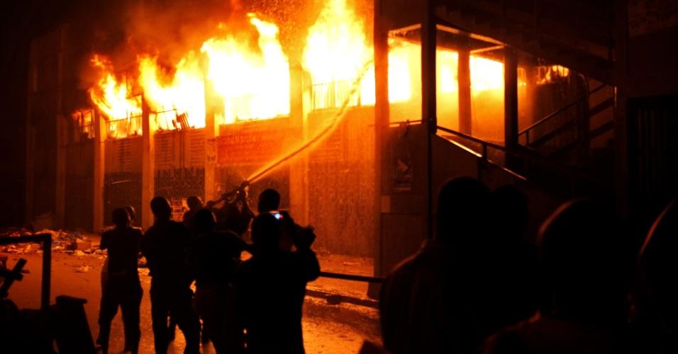 11.jan.2013 - Bombeiros tentam apagar um incêndio no Grande Mercado de Lome, no sul de Togo. Uma multidão se reuniu ao redor do prédio, enquanto alguns lojistas tentavam entrar para salvar os produtos