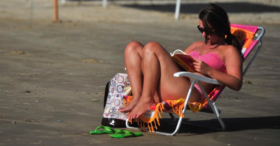 12.jan.2013 - Banhista aproveita dia de sol para ler em praia no norte do Rio Grande do Sul
