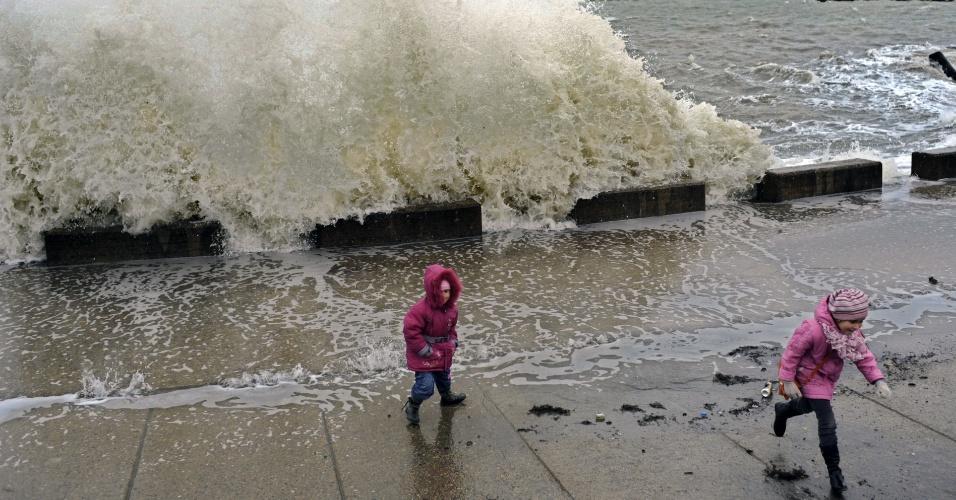 12.jan.2013 - Crianças correm de onda forte em cidade litorânea da Rússia