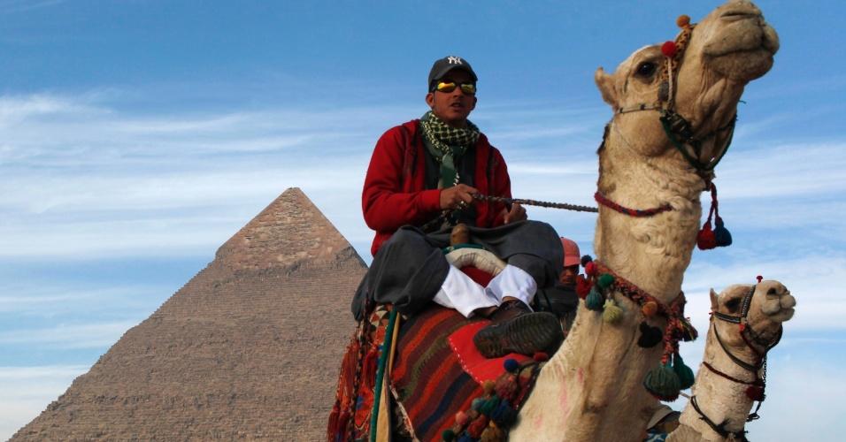 12.jan.2013 - Homem passeia com camelo em frente a pirâmide na cidade do Cairo, no Egito