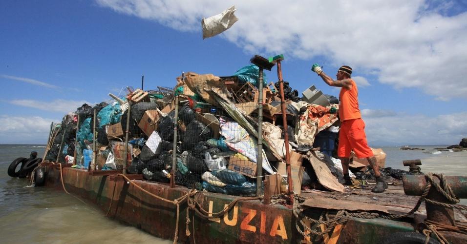 12.jan.2013 - Homens retiram lixo produzido por moradores da Ilha do Mel, no litoral do Paraná; a ação faz parte da Operação Verão Paraná criado pelo governo do estado para auxiliar os municípios.