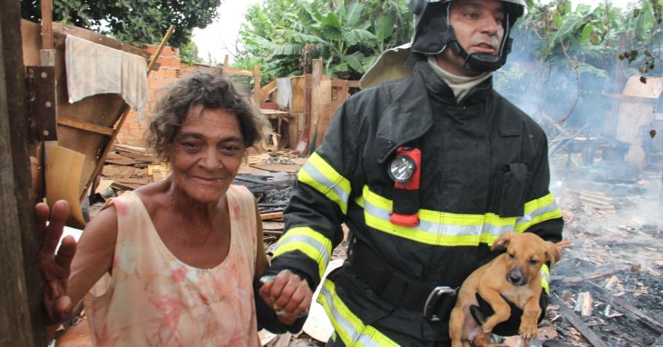 12.jan.2013 - Bombeiro socorre mulher e cachorro em incêndio que atingiu dos barracos em favela de Ribeirão Preto; ainda não há informações sobre vítimas e sobre o que teria iniciado o incêndio