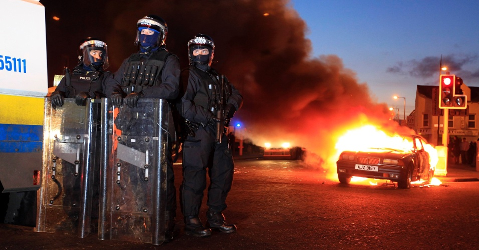 12.jan.2013 - Policiais são vistos ao lado de carro em chamas durante conflitos no leste de Belfast, na Irlanda do Norte, neste sábado (12)