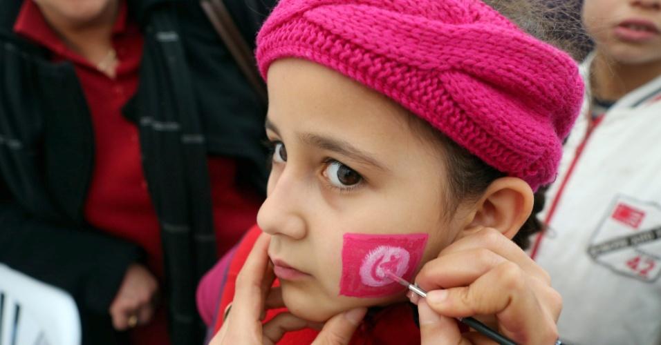 13.jan.2013 - Manifestante pinta a bandeira da Tunísia no rosto de menina durante as celebrações do segundo aniversário da queda do presidente Ben Ali, na avenida Habib Bourguiba, em Túnis, neste domingo (13). A queda de Ben Ali do poder deu início à Primavera Árabe, onda de protestos contra governos autocráticos que levaram à deposição de presidentes de outros países, como Egito e Líbia