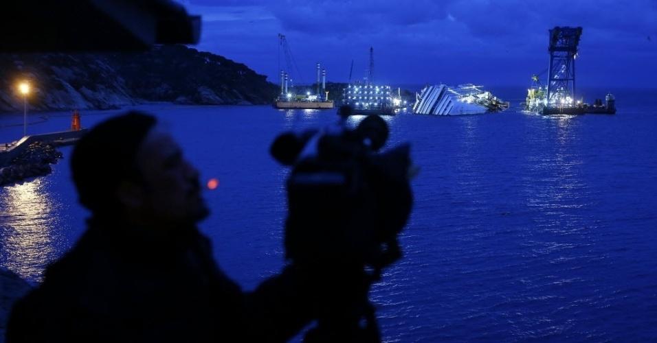 13.jan.2013 - Camêra filma navio Costa Concordia, que naufragou há exato um ano e deixou 32 pessoas mortas, na costa da Toscana (Itália). Rodeada de guindastes, a embarcação deve ser retirada do local abracação