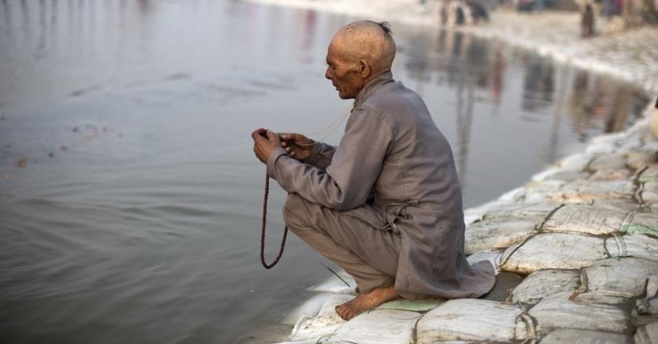 """13.jan.2013 - Devoto hindu segura terço às margens do rio Ganges durante o festival """"Kumbh Mela"""", em Allahabad, no  nordeste da Índia"""
