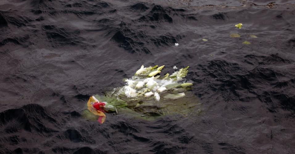 13.jan.2013 - Flores são jogadas ao mar em homenagem aos mortos no acidente do Costa Concordia. Após um ano do naufrágio que deixou 30 mortos e dois desaparecidos na costa italiana, o navio continua atracado no mesmo lugar e deve demorar para ser retirado