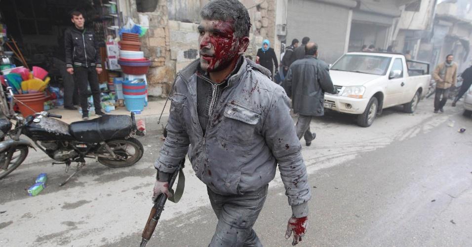 13.jan.2013 - Homem com arma caminha ferido em Aleppo, na Síria, após um ataque a bomba aéreo