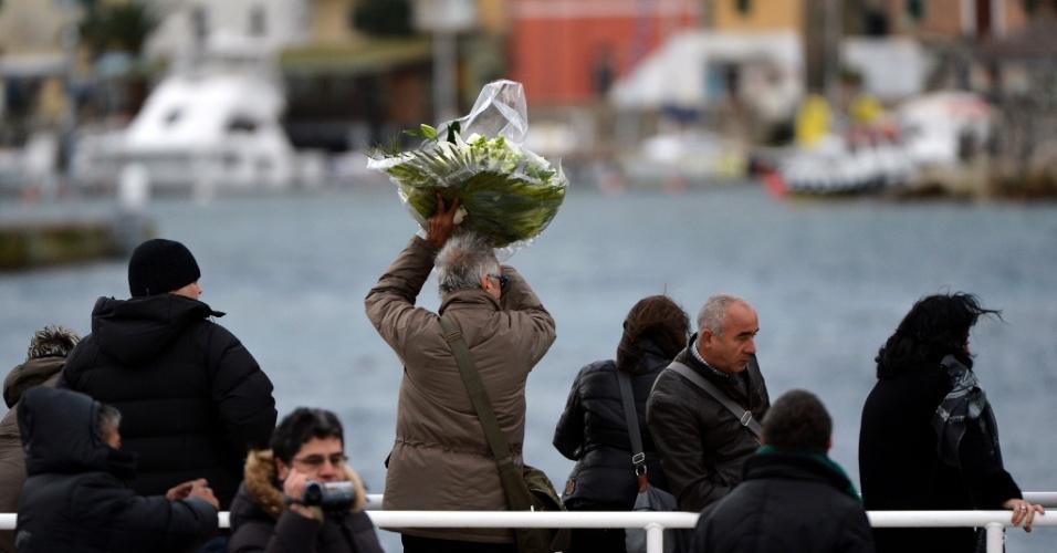 13.jan.2013 - Homem joga buquê de flores ao mar em homenagem aos mostos no acidente com o navio Costa Concordia. Após um ano do naufrágio que deixou 30 mortos e dois desaparecidos na costa italiana, o navio continua atracado no mesmo lugar e deve demorar para ser retirado