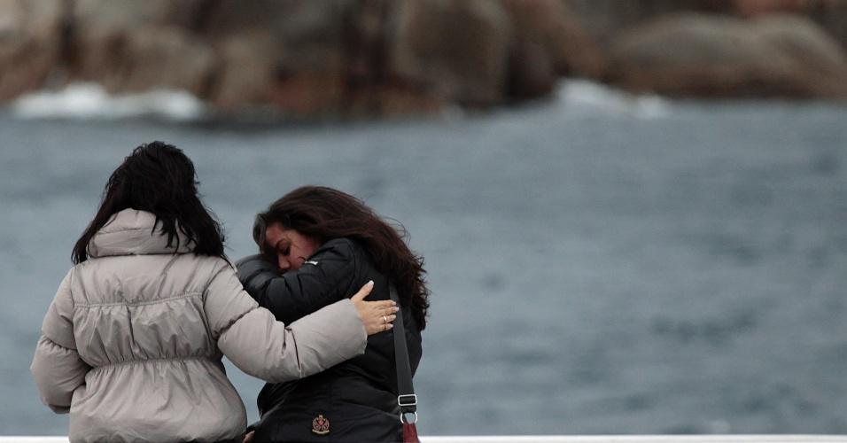 13.jan.2013 - Jovens choram ao olhar para o navio Costa Concordia. Após um ano do naufrágio que deixou 30 mortos e dois desaparecidos na costa italiana, o navio continua atracado no mesmo lugar e deve demorar para ser retirado