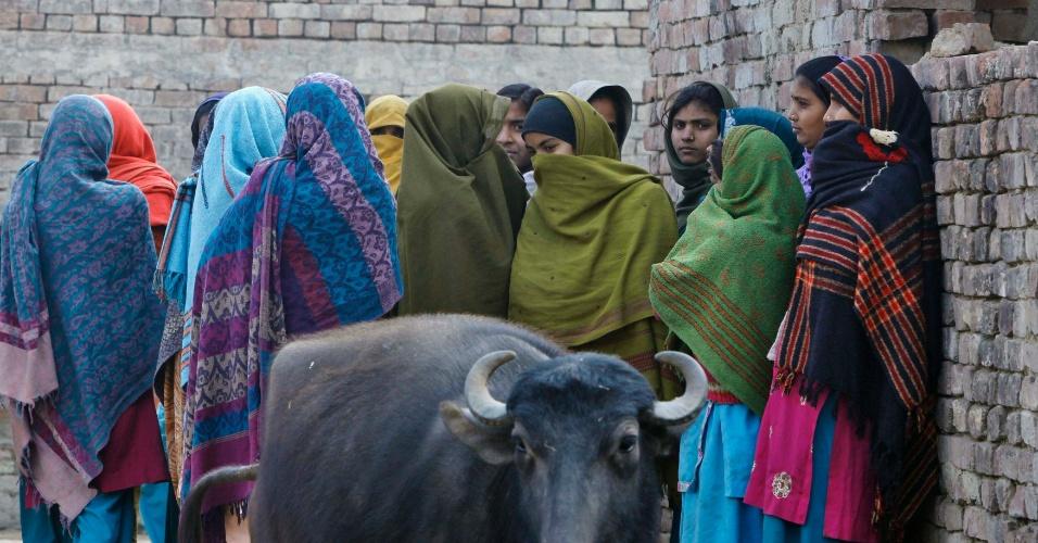 12.jan.2013 - Vizinhos da mãe do menor acusado no caso de estupro coletivo, em Nova Déli, reúnem-se fora de sua casa na aldeia no norte do estado indiano de Uttar Pradesh. Cinco homens foram indiciados por acusações que incluem homicídio, estupro e sequestro. Um sexto envolvido está sendo investigado separadamente, para determinar se é de fato menor de 18 anos, como ele diz ser. Caso isso seja confirmado, ele deve ser submetido a um juizado de menores, e poderá ser internado em um reformatório por até três anos