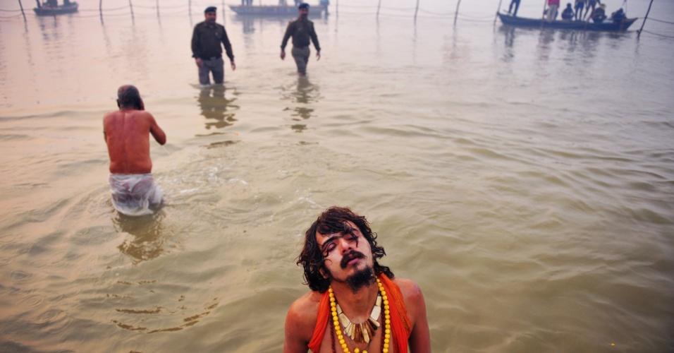 14.jan.2013 - Devoto hindu fecha os olhos e ora enquanto se banha na confluência dos rios Ganges, Yamuna e Saraswati no primeiro dia do festival Kumbh Mela, em Allahabad, na Índia. Milhões de peregrinos hindus são esperados para participar da grande congregação religiosa de um período de mais de um mês nas margens do rio Sangam