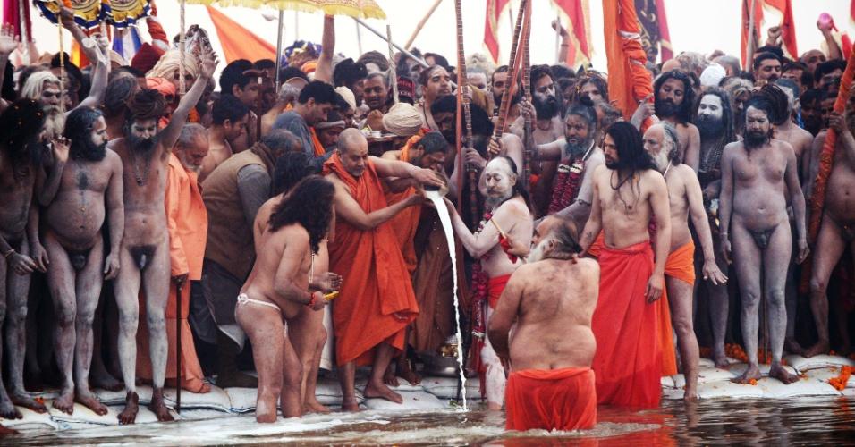14.jan.2013 - Líder indiano derrama leite em devotos na confluência do rios Ganges, Yamuna e Saraswati no primeiro dia do festival Kumbh Mela, em Allahabad, na Índia. Milhões de peregrinos hindus são esperados para participar da grande congregação religiosa de um período de mais de um mês nas margens do rio Sangam