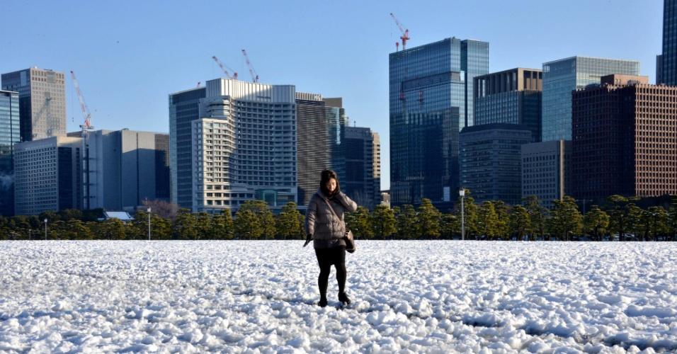 15.jan.2013 - Mulher caminha com cuidado através de um campo coberto de neve no parque diante do Palácio Imperial japonês, um dia após uma forte nevasca atingir a região metropolitana de Tóquio. Uma pessoa morreu e ao menos 463 tiveram ferimentos devido à forte nevasca